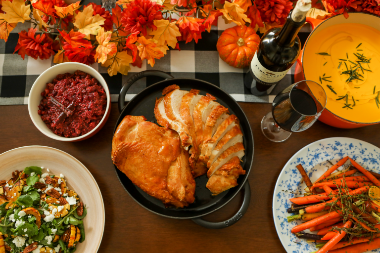 a thanksgiving table setting with roasted turkey front and center