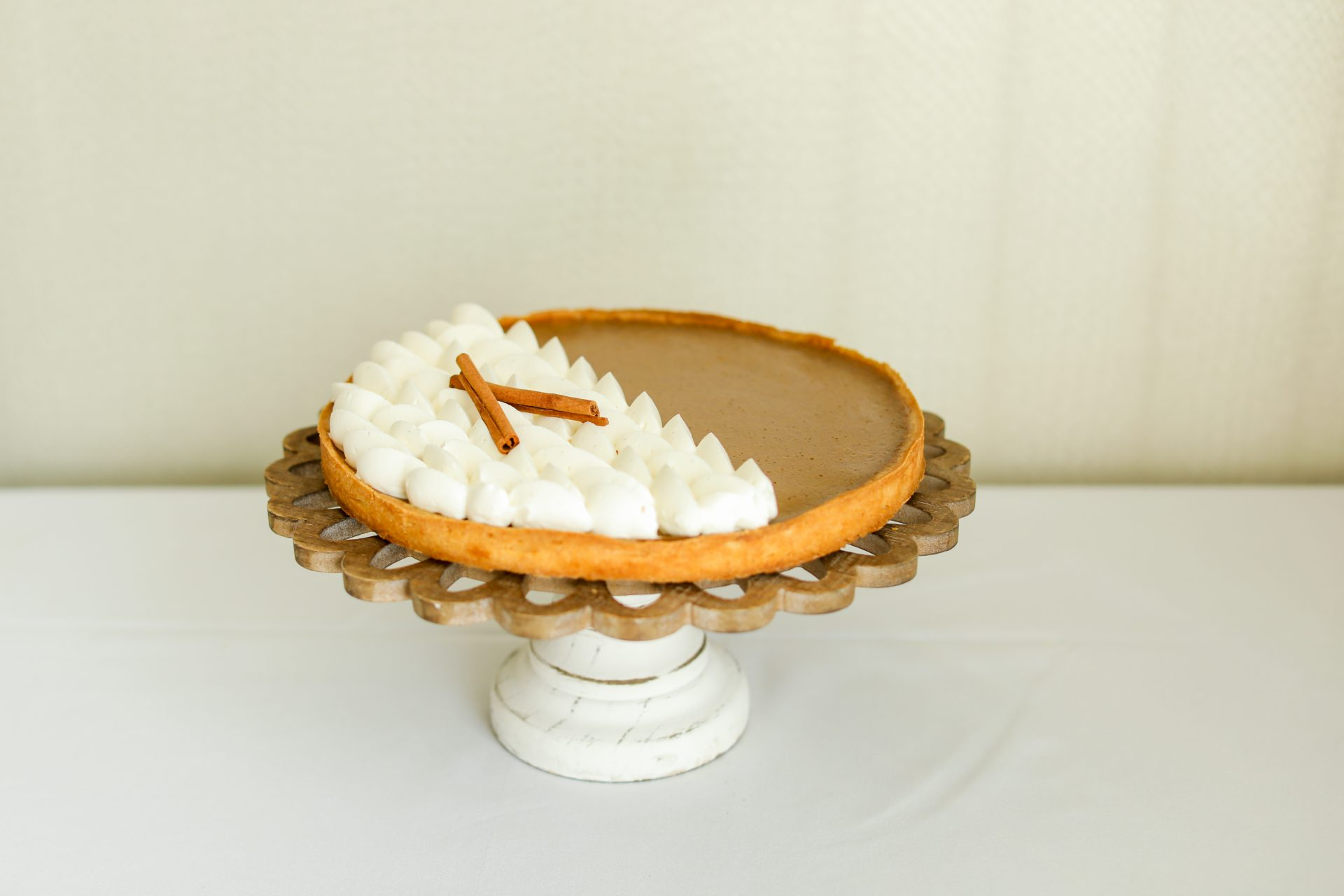 pumpkin pie adorned with chantilly cream and cinnamon stick displayed on a wooden stand