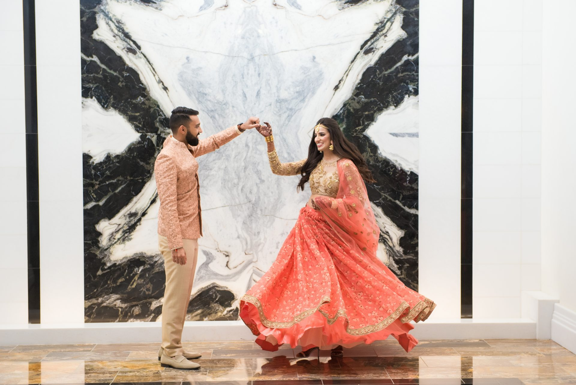an indian couple holding hands at fairmont austin in front of a marble wall