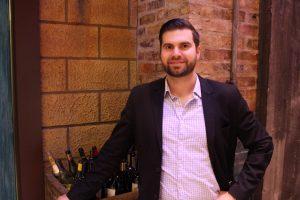 fairmont austin beverage director andrew grenz standing next to a case of wine