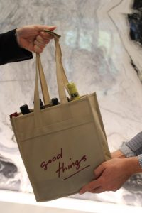 good things wine tote being filled with six bottles of wine being handed to a guest
