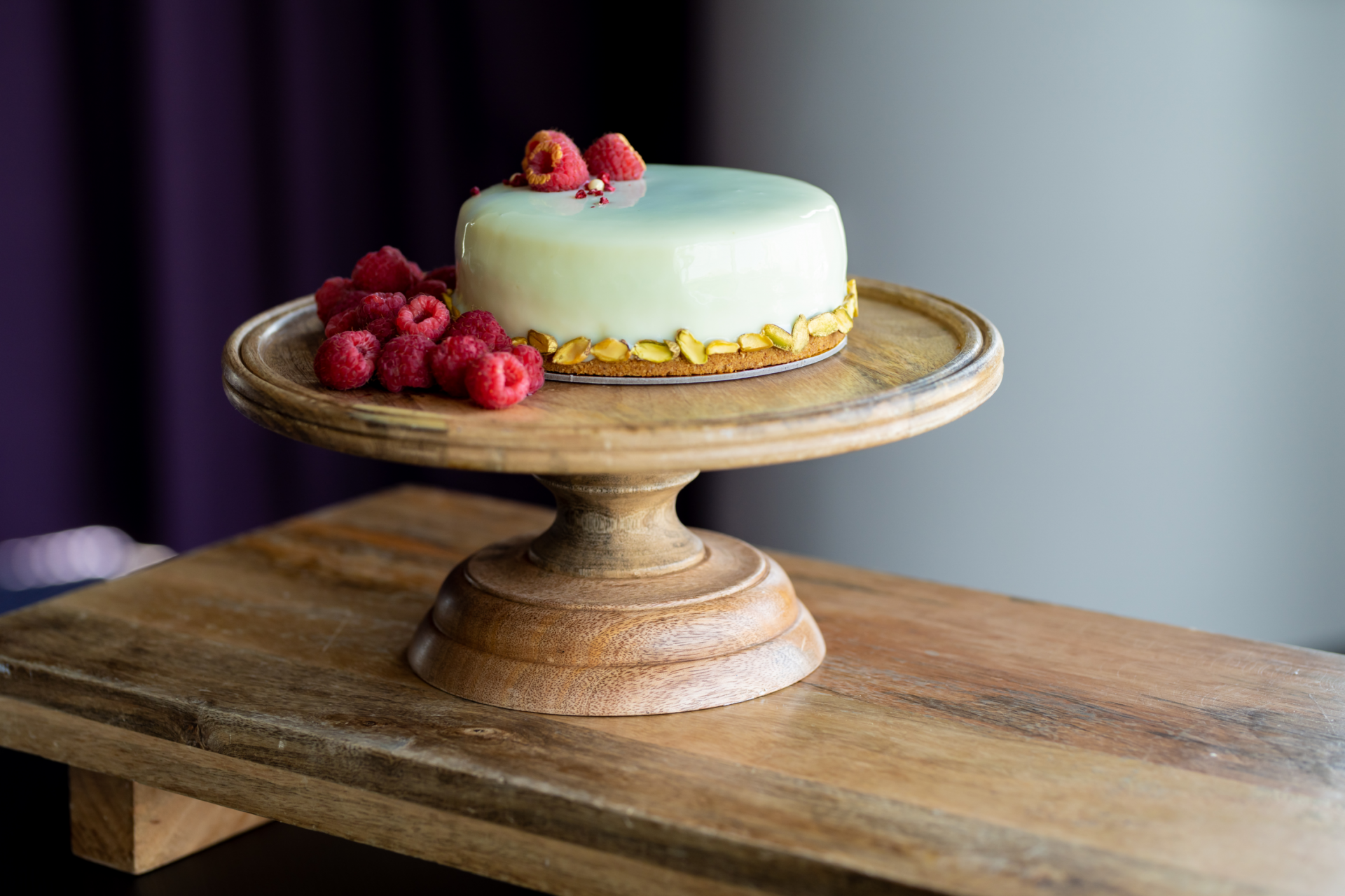 a pistachio cheesecake displayed on a wooden cake plate garnished with fresh raspberries and pistachios