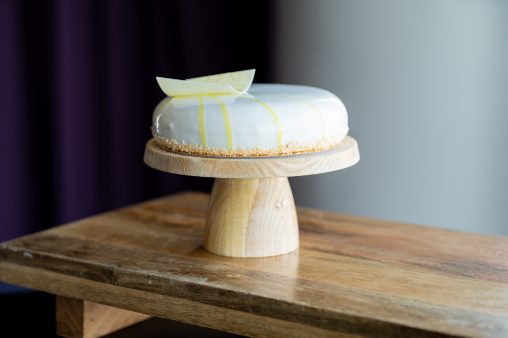 a banana coconut entremets cake displayed on a wooden cake stand garnished with an almond daquoise and coconut