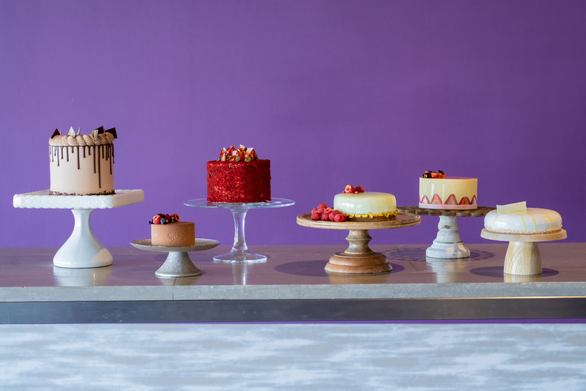 an assortment of six gourmet cakes on cake stands with a purple background
