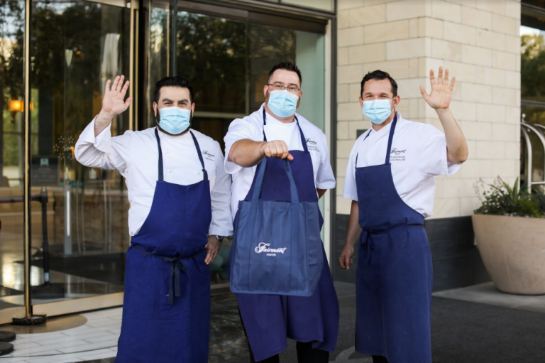 chefs andre natera, benjamin metais and graeme little wearing aprons and waving outside of fairmont austin