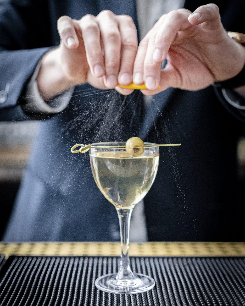fulton bartender garnishing a martini at the bar