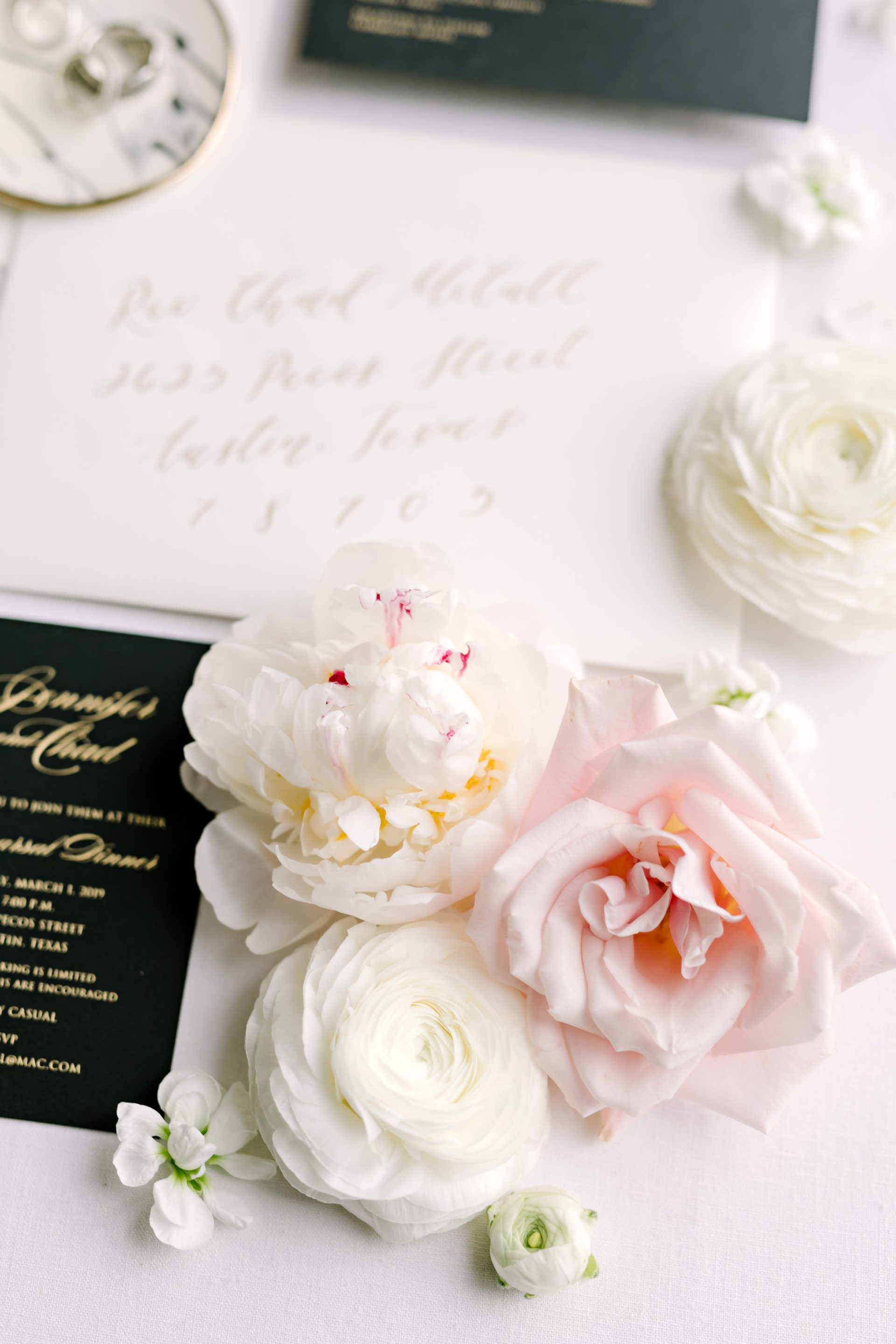 pink and white flowers resting next to a wedding invitation