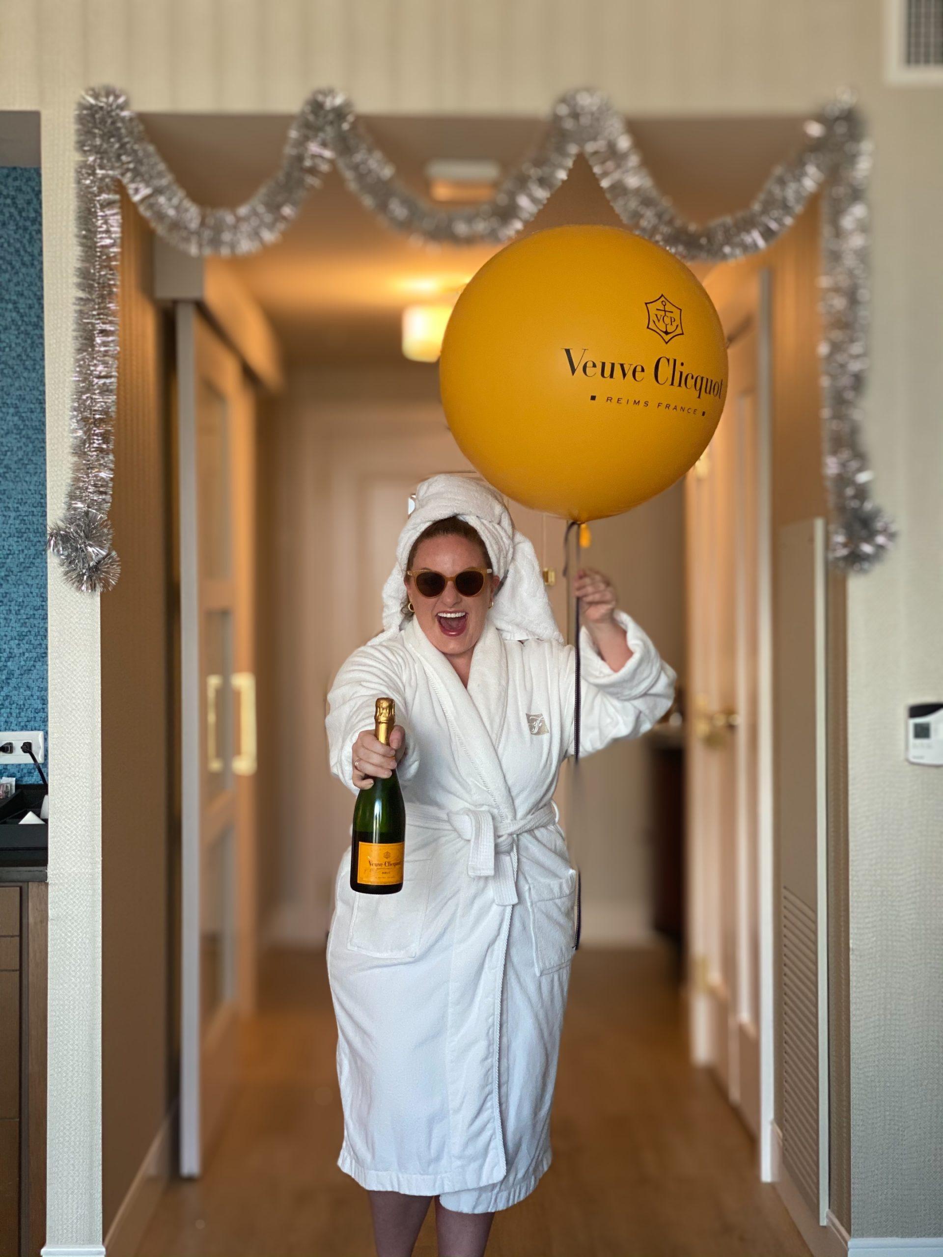 a woman in a robe holding veuve clicquot in fairmont austin sparkle suite