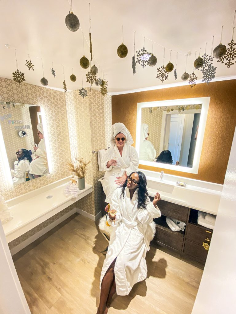 two women in robes enjoying a sparkly decorated bathroom in fairmont austin's sparkle suite