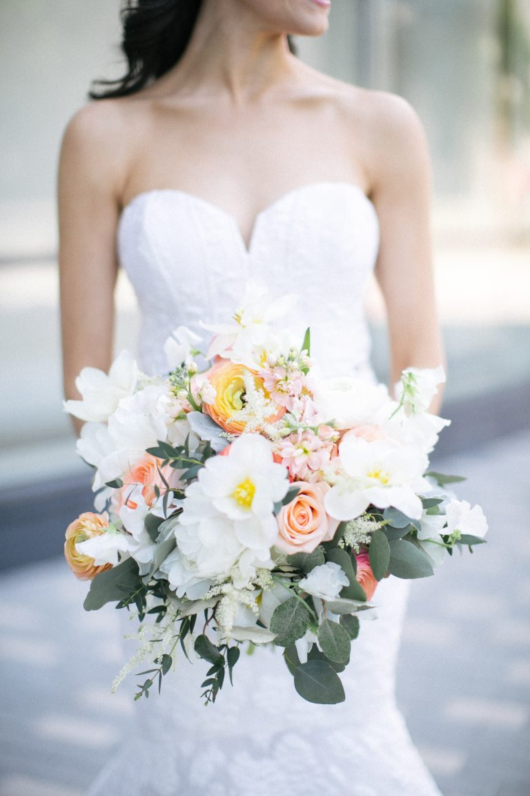 a woman in a wedding dress and holding a beautiful bouquet of flowers